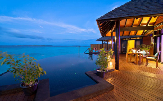 Sunset view of water villa with pool